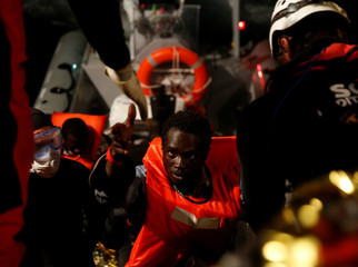 A migrant rescued from a rubber dinghy is helped aboard the MV Aquarius, a search and rescue ship run in partnership between SOS Mediterranee and Medecins Sans Frontieres, in the central Mediterranean 69 nautical miles off the coast of Libya
