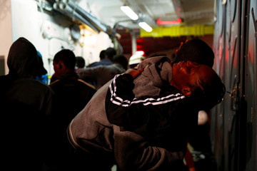Migrants embrace on the deck of MV Aquarius, a search and rescue ship run in partnership between SOS Mediterranee and Medecins Sans Frontieres, after being rescued in the central Mediterranean, 69 nautical miles off the coast of Libya