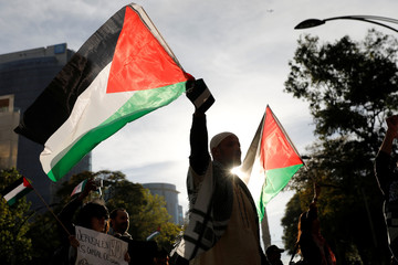 A member of the Islam community holds a Palestinian flag next to supporters of Palestine while demonstrating against U.S. President Donald Trump's recognition of Jerusalem as Israel's capital, outside the U.S embassy in Mexico City