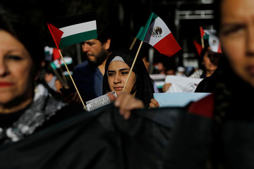 A woman holds a Palestinian and Mexican flag next to supporters of Palestine while demonstrating against U.S. President Donald Trump's recognition of Jerusalem as Israel's capital, outside the U.S embassy in Mexico City