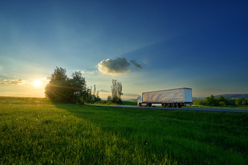 Fotobehang - White truck driving on the road between green meadows in a rural landscape at sunset