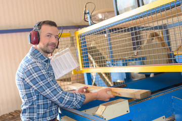 Man putting plank of wood through machine