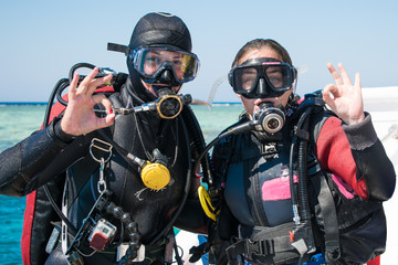 two happy divers in wetsuits and masks with octopus in mouthes on the background of azure sea show ok . happy girls in wetsuits. scuba diving. diving. divers