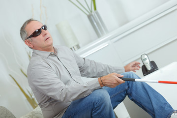 mature blind man with stick and dark glasses at home