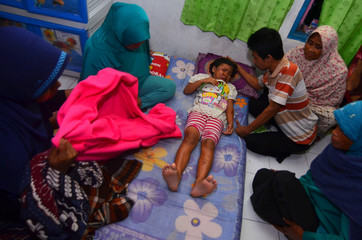 A man calms his injured daughter after an earthquake hit Sumelap village in Tasikmalaya, Indonesia
