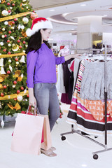 Caucasian woman choosing dresses for Christmas gift