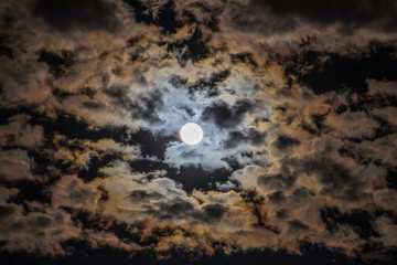 Bright moon in the night sky surrounded by colorful clouds