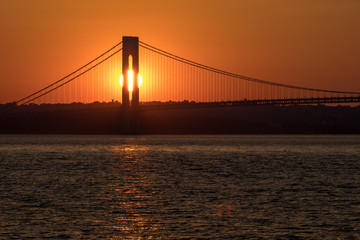 Sunset over horizon behind big bridge, red sunlight background, sun path on water