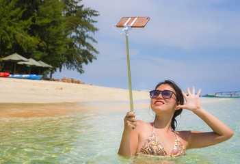 young beautiful and happy Asian Chinese woman having fun on sea water taking selfie picture with mobile phone camera on paradise beach