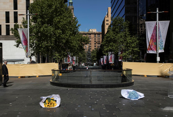 Flowers lie on the ground at the site of a permanent memorial honouring the lives of cafe manager Tori Johnson and barrister Katrina Dawson, victims of the 2014 siege at Lindt Cafe, in Martin Place, Sydney, Australia