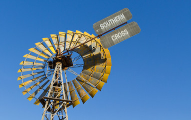 Yellow windmill against a bright blue sky