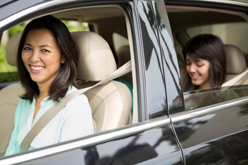 Happy Asian mother driving her teen daughter.