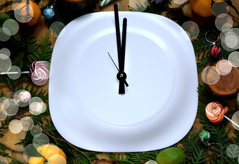 Clock arrows on a white plate surrounded by Christmas attributes. Concept of New Year coming