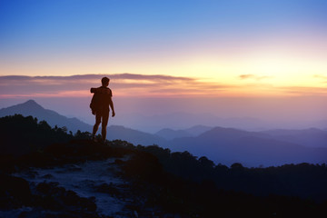 Man's silhouette on sunset mountains backdrop