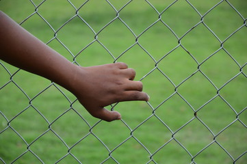 chain link fence with man hand, selective focus.