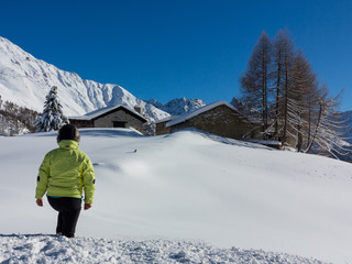 Hiker watching panorama, winter landscape. Snow and chalet in mountain