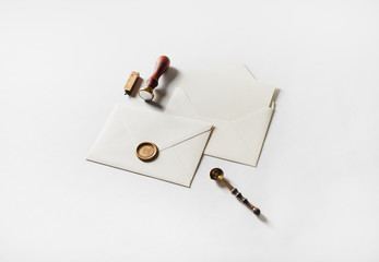 Letter envelope with golden wax seal, stamp, spoon and postcard on white paper background.