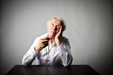 Old man is praying with rosary beads.