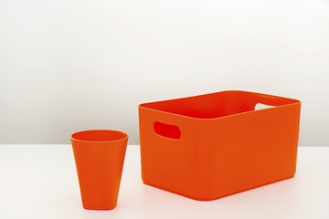 Orange plastic box and cup for domestic use on white table.