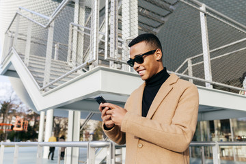 Cheerful black man with smartphone