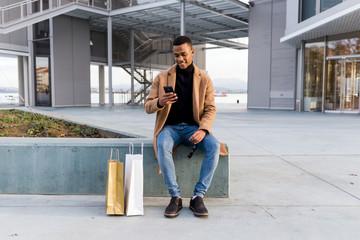 Stylish black man browsing smartphone