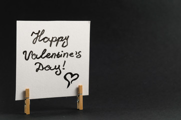 The sticker with the greeting happy Valentines day on the clothespin on a dark background