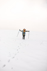 Wide view on the snowy hill with footprints and hiker walking up with backpack in the mountains