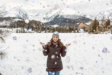 Tourist woman with falling petals in Strbske pleso, Slovakia, winter