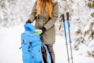 Woman having a break getting a lunch box from the backpack at the snowy forest during the winter hiking