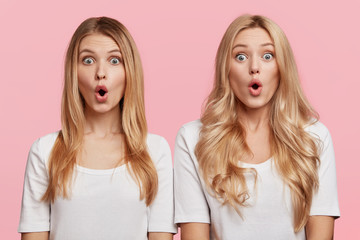 Two surprised blonde sisters stand next to each other, keep mouth opened and stare at camera, dressed casually, shocked to recieve bad shocking news from parents. Amazed females isolated on pink wall