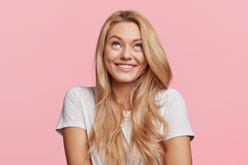 Cheerful blonde female looks upwards, has shining smile, thoughtful expression, dressed in casual white t shirt, isolated over pink studio background. Beautiful young woman dreams about something Wall mural