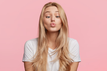 Blonde attractive female makes grimace, foolishes in studio, crosses eyes and rounds lips, has fun after being tired at classes, isolated over pink background. Beautiful woman makes fool indoor