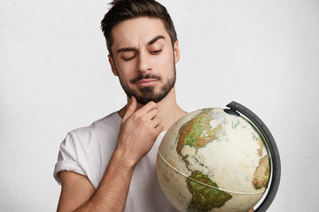Portrait of thoughtful bearded businessman wants to explore unknown places, looks at worldwide globe, tries to choose destination, isolated over white concrete wall. Young male holds earth indoor