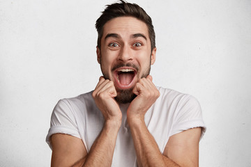Excited joyful bearded male looks with amazement at camera, being overjoyed as sees unexpected surprise, isolated over white concrete background. People, facial expressions and happiness concept
