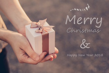 Time gifts - gift box in hand for Christmas with MERRY CHRISTMAS and HAPPY NEW YEAR 2018 /soft focus picture / Vintage concept