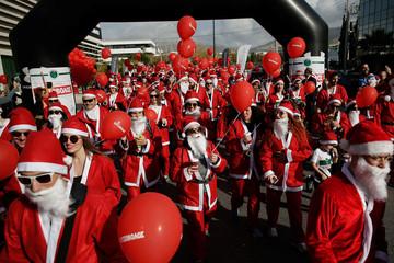 People dressed as Santa Claus take part in a Santa Claus Run in Glyfada suburb, Athens