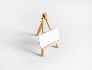 Photo of blank business card on wood holder at white paper background.