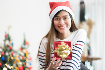 Asia woman smile holding gold xmas gift box at holiday party with decoration flag at background,present giving Christmas party present,winter holiday happiness moment.
