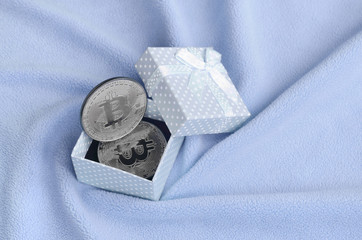 The silver bitcoin lies in a small blue gift box with a small bow on a blanket made of soft and fluffy light blue fleece fabric with a large number of relief folds