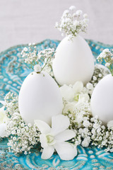 Decoration with goose egg, orchid flowers and gypsophila paniculata twigs.