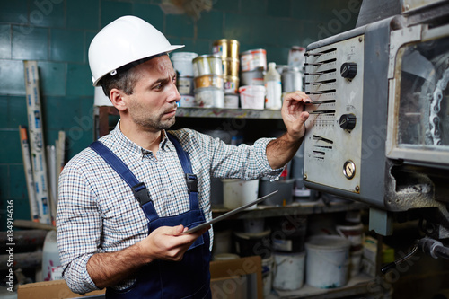 repairman or technician in uniform checking regulators on control panel of inductrial machine