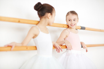Two little ballerinas leaning at bars and having talk after ballet classes