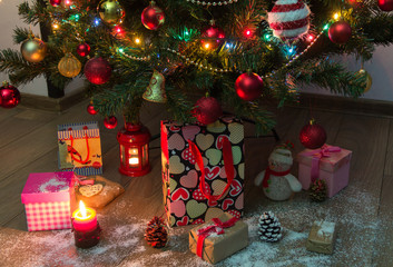 Christmas decoration. Christmas gifts with a candle and a lantern under Christmas tree