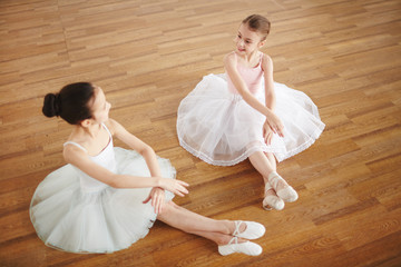 Cute little ballerinas in white shiffon skirts sitting on the floor and exercising