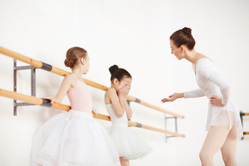 Ballet teacher explaining crying little girl what her problem is after training