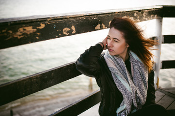woman on a cold day wrapped in a scarf on the beach