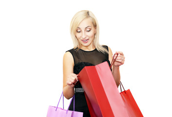 blonde girl happily opens her shopping bag isolated on white background