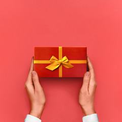 Gift box Bright styled photo Female hands are holding a red gift box with yellow ribbon in gesture of giving on pink background Top view Photo mockup with space for text