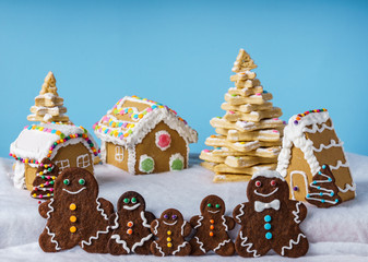 home made delicious traditional gingerbread village and gingerbread man family blue background.