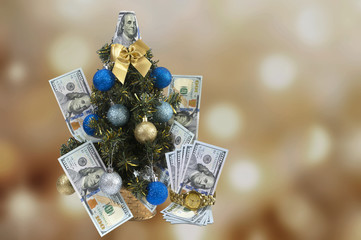 Christmas tree with dollars on a brown background.